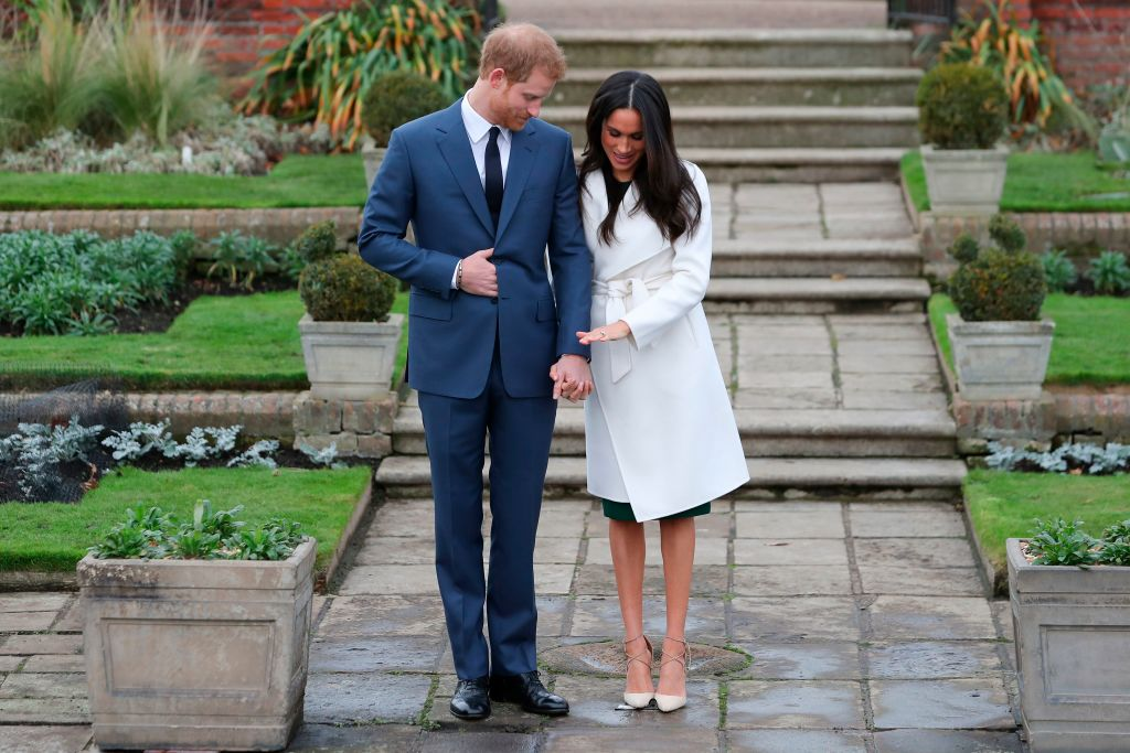 Britain's Prince Harry stands with his fiancée US actress Meghan Markle as she shows off her engagement ring