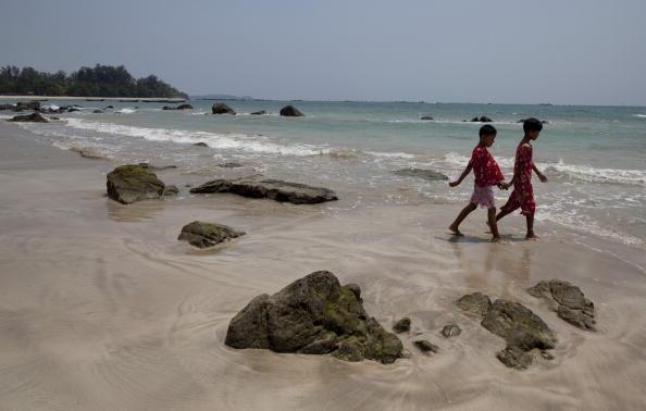 Burmese children walk along an empty beach on May 5, 2009 on Nagapali Beach along the Bay of Bengal in Myanmar (also called Burma)