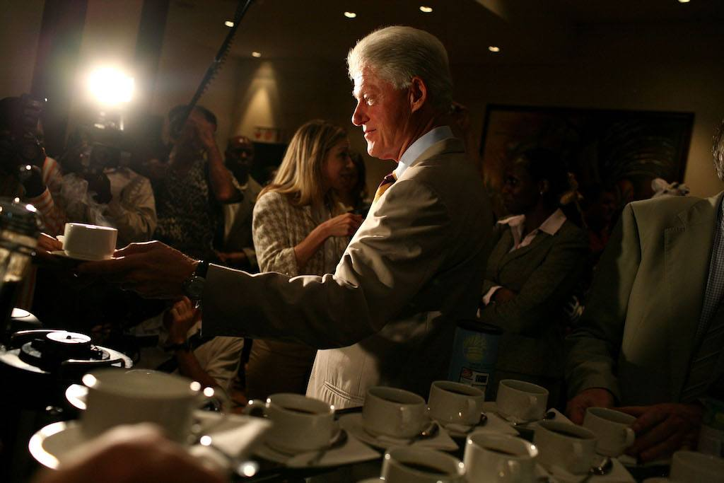 Bill Clinton samples coffee as his daughter Chelsea Clinton looks on.