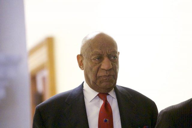 Bill Cosby wearing a black suit and red tie.
