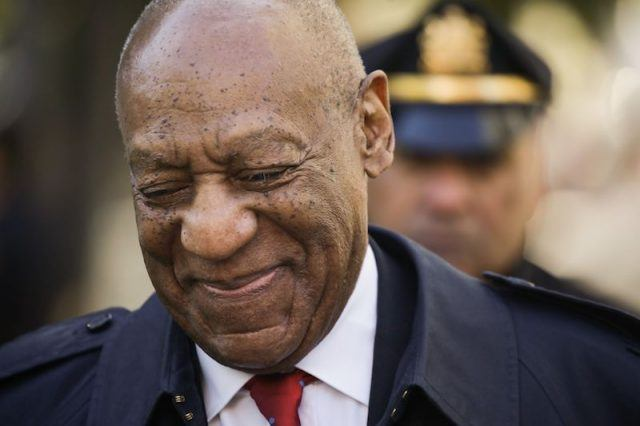 Bill Cosby smiling and looking towards the floor.