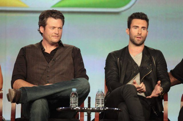 Blake Shelton and Adam Levine sitting on stage during the TCA Winter Tour.