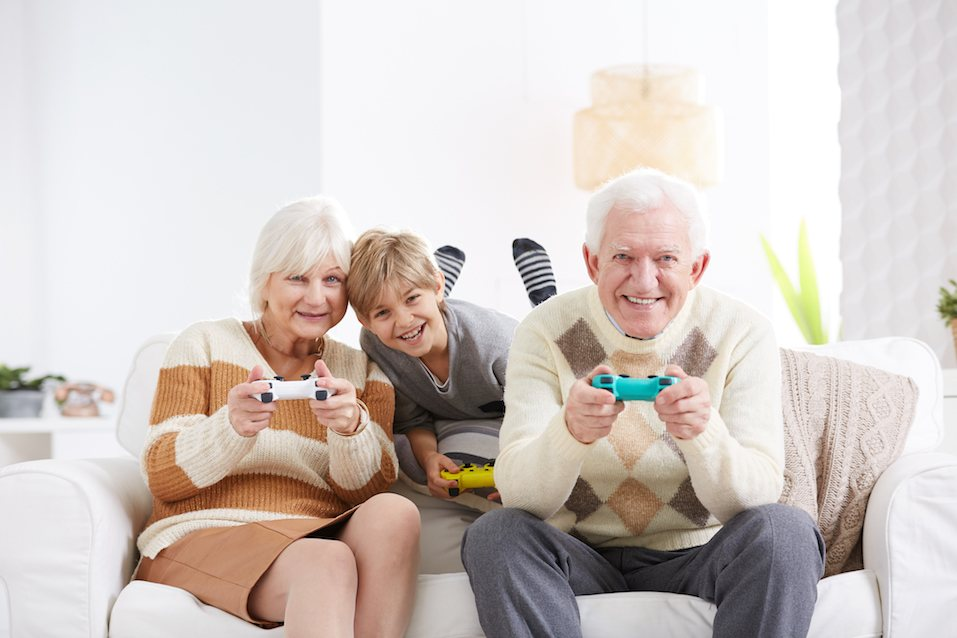 Boy playing video games with his grandparents