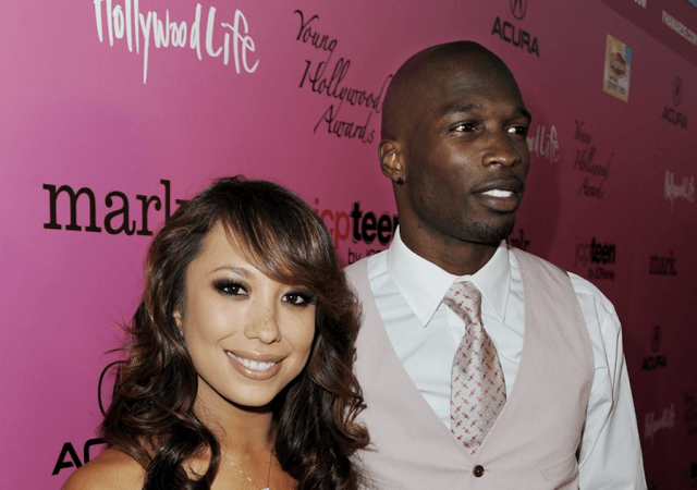 Chad Ochocinco Johnson and Cheryl Burke posing together on a red carpet event.