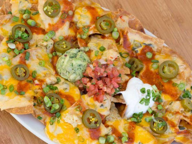 Nachos loaded with cheese, cream and toppings.