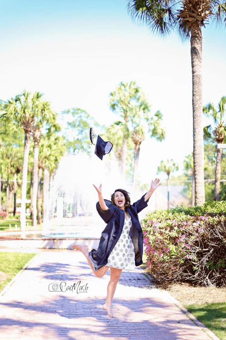 Girl jumping in her graduation photo