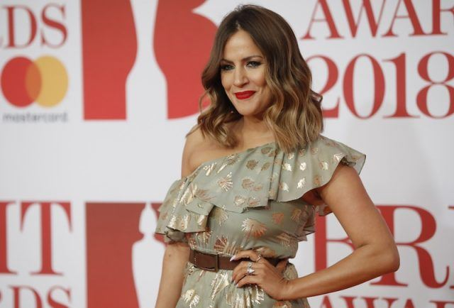 Caroline Flack posing with one hand on her hip on a red carpet.