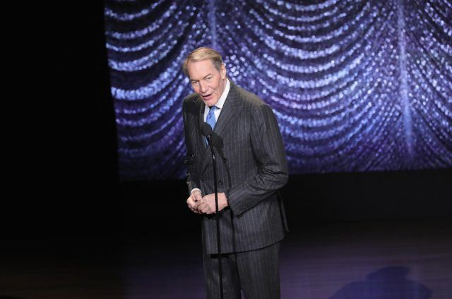 Charlie Rose speaking into a microphone on stage.