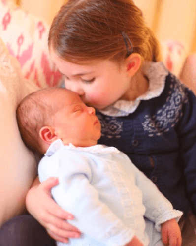 Princess Charlotte kissing Prince Louis' head.