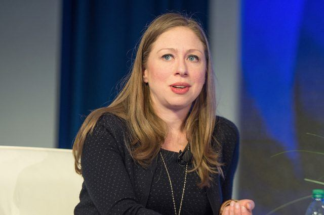 Chelsea Clinton sitting on a couch.