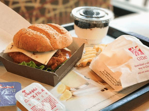 A sandwich from Chick-fil-A with fries and sauce