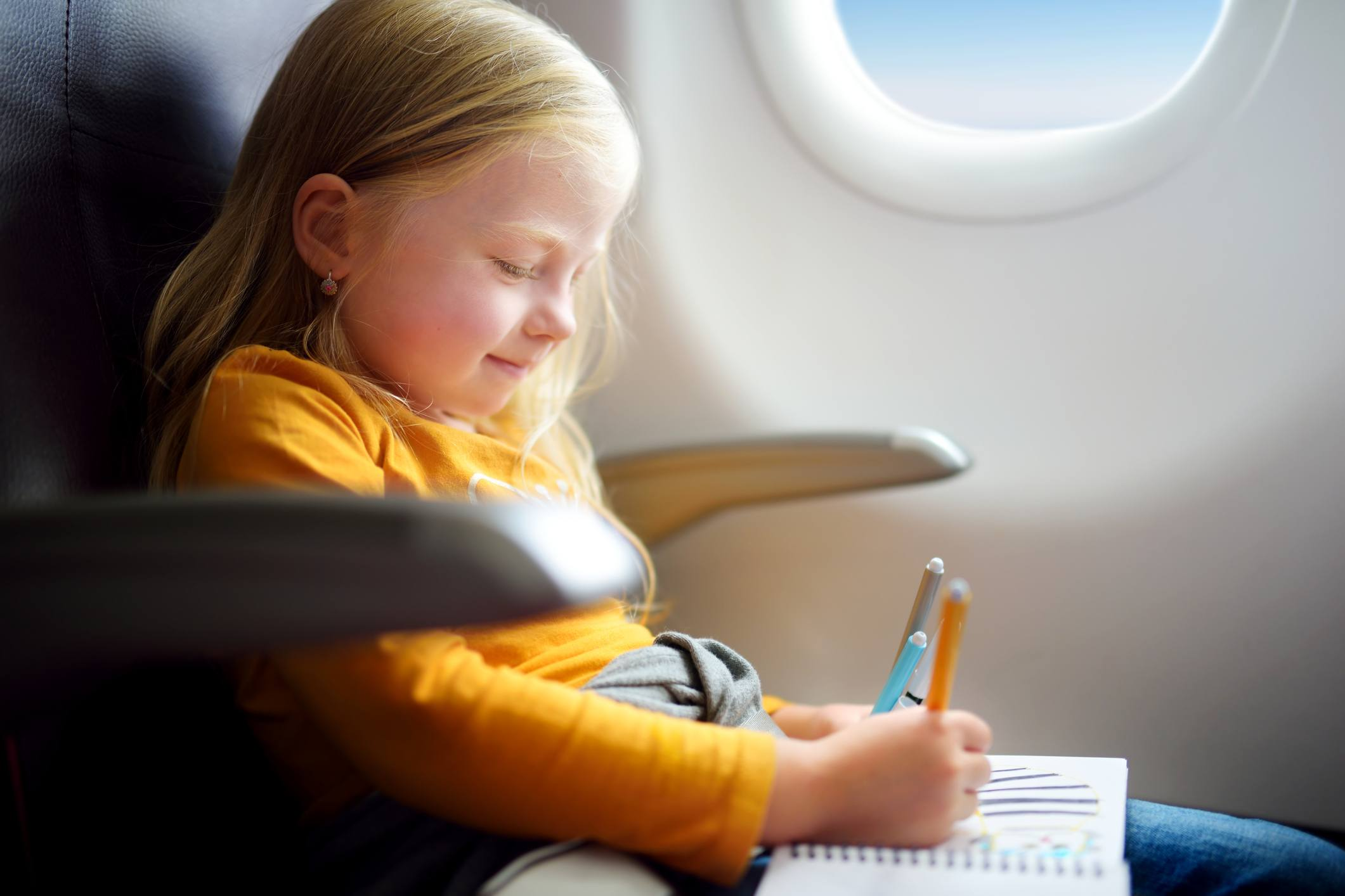 Adorable little girl traveling by an airplane. Child sitting by aircraft window and drawing or coloring a picture with felt-tip pens.
