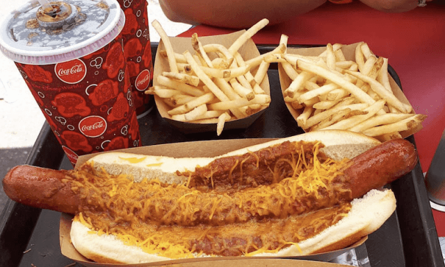 A chili cheese hot dog with beverages and fries.