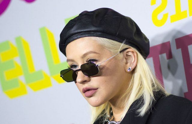 Christina Aguilera on a red carpet, wearing black sunglasses and a black beret.