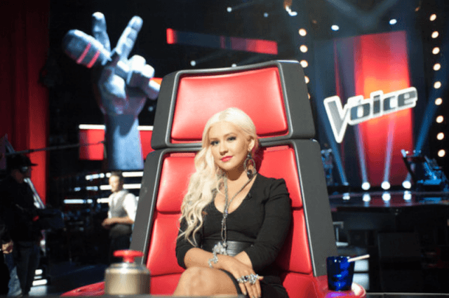 Christina Aguilera sitting on a red chair on 'The Voice'.