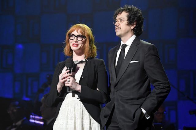 Christina Hendricks and Geoffrey Arend speaking on stage while standing closely together.