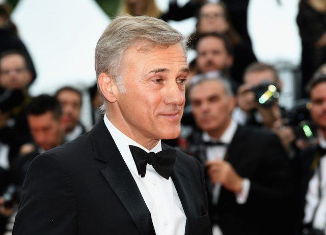Christoph Waltz posing on a red carpet while in a tuxedo.