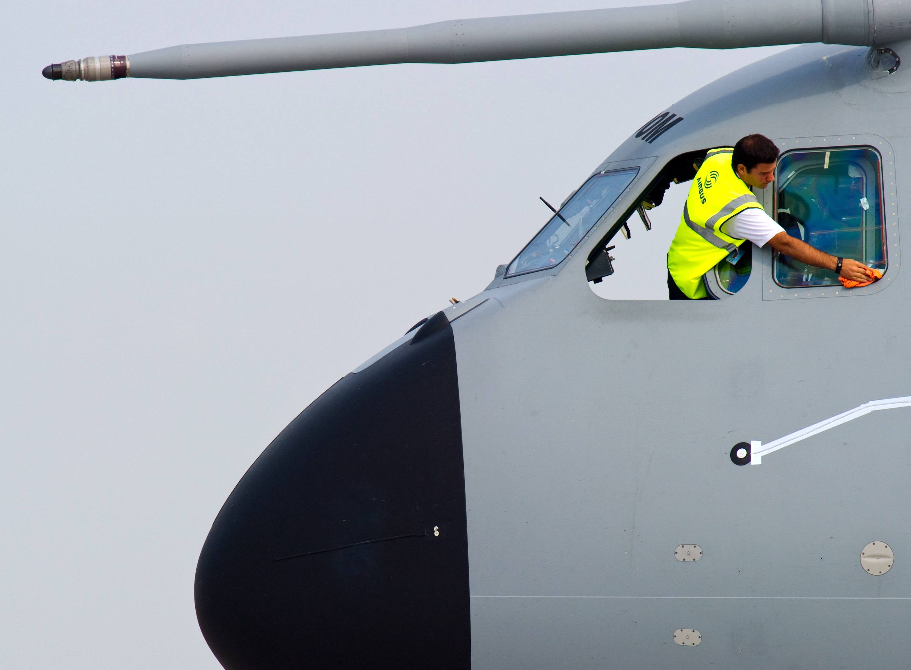 A man cleans the cockpit windows of an Airplane