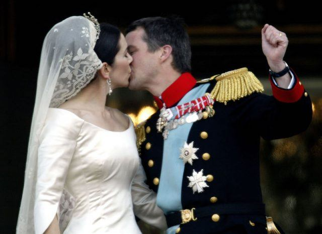 The couple kisses on the balcony on their wedding day.