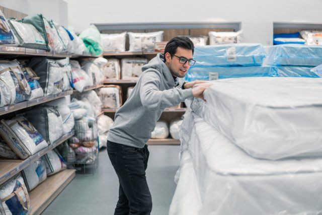 Customer man chooses bed linen in the supermarket mall store.