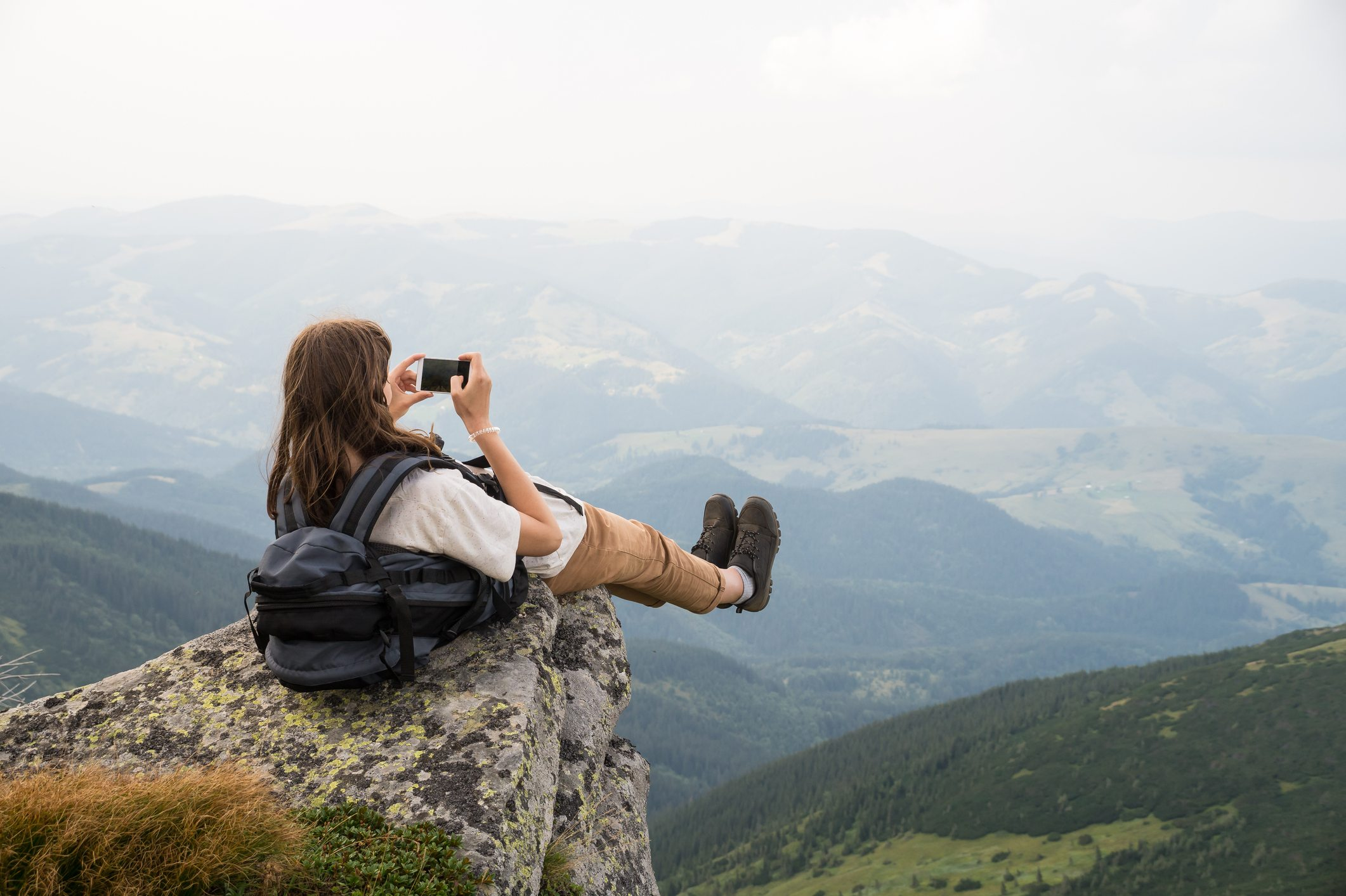 Female tourist takes photo of legs with cell phone from top of the mountain cliff
