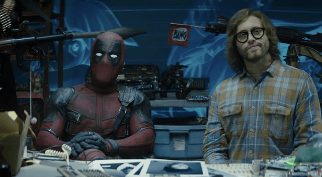 Deadpool sitting at a desk while he waits for new members to judge.