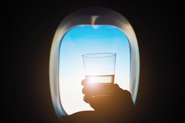 A person holding up a cup while on a plane.