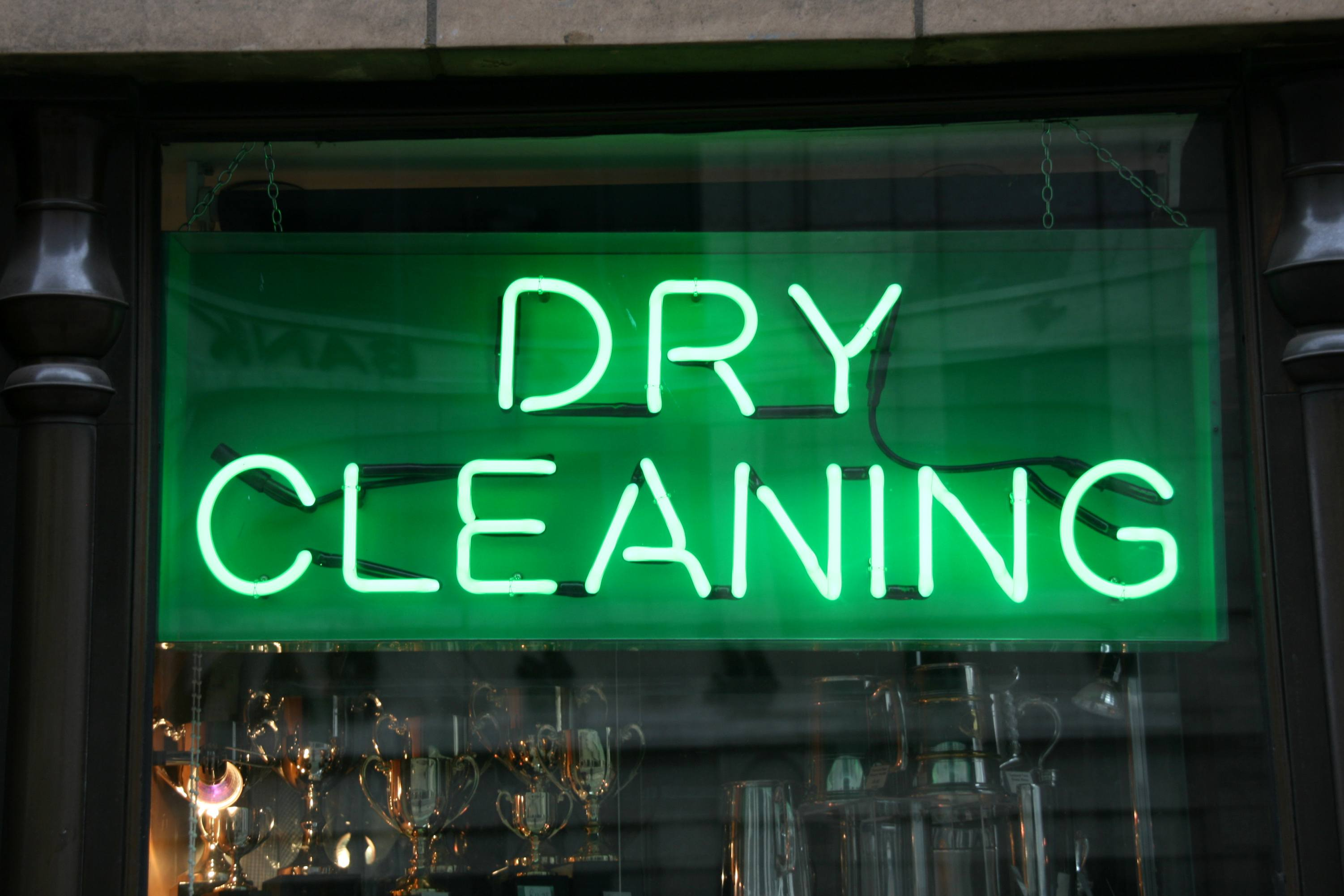 Close-up of a neon green dry cleaning sign in a window