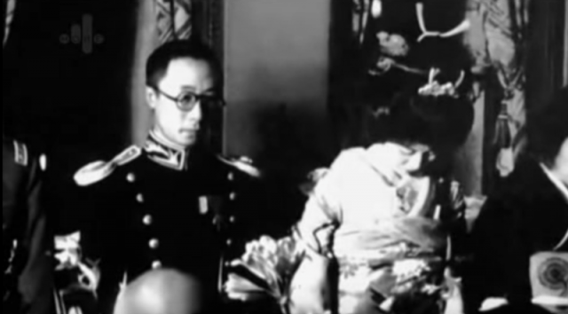 Emperor Puyi and Empress Gobulo Wan Rong in footage of a ceremony.