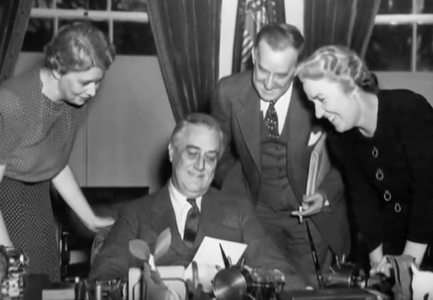 Franklin Delano Roosevelt holding a document and smiling with others around him