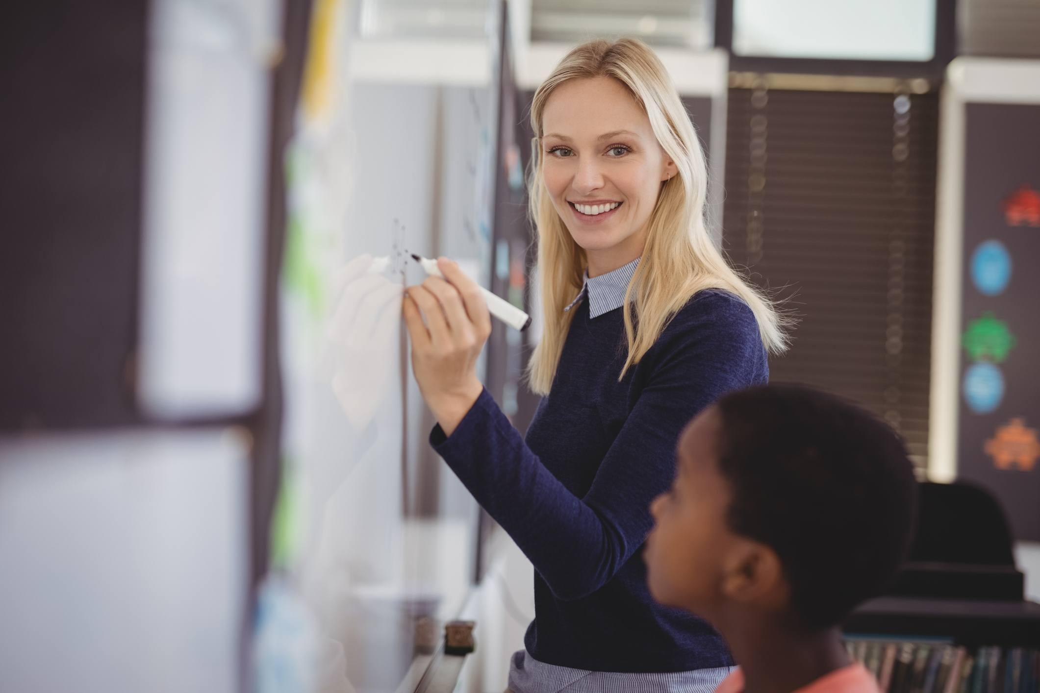 Portrait of teacher assisting schoolboy on whiteboard in classroom