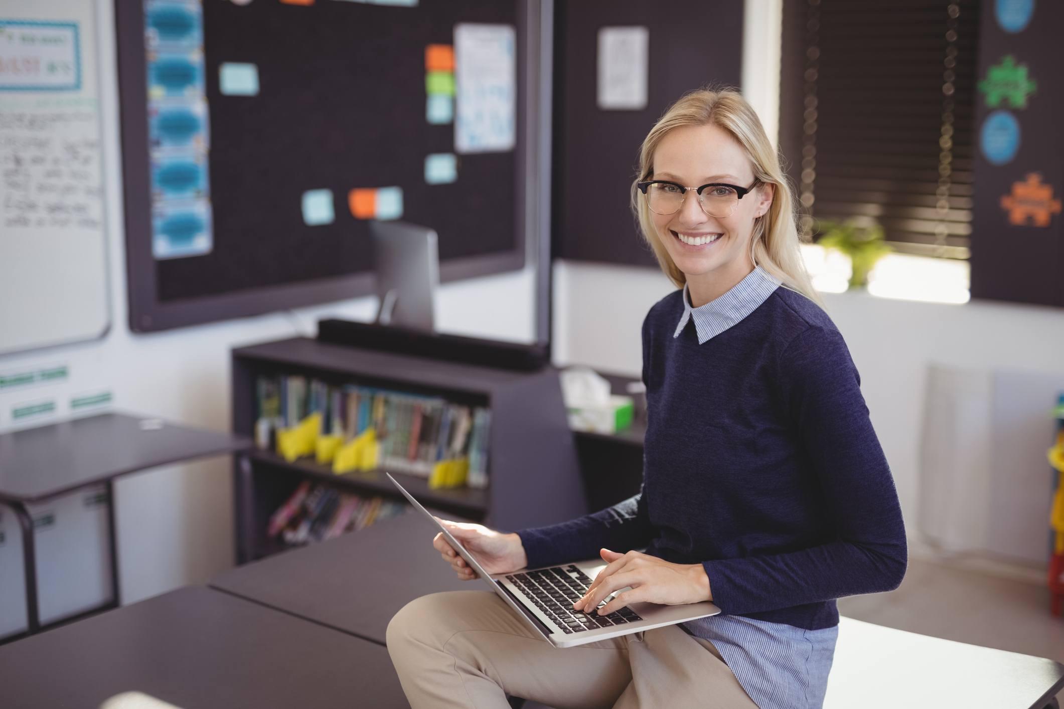 Portrait of happy teacher using laptop in classroom