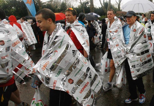 Competitors walk from the finish line wrapped in space blankets