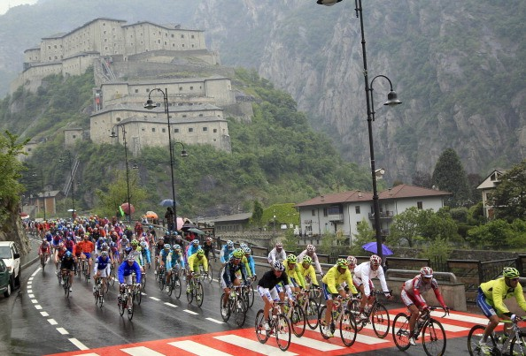 The pack rides with the Fort of Bard in the background during the 14th stage of the Tour of Italy cycling race