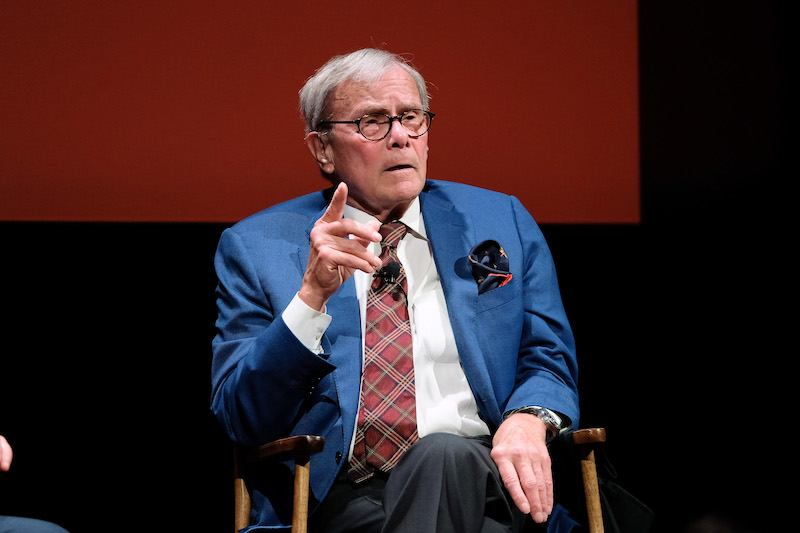 Tom Brokaw sitting on a chair and pointing a finger as he speaks to the audience.