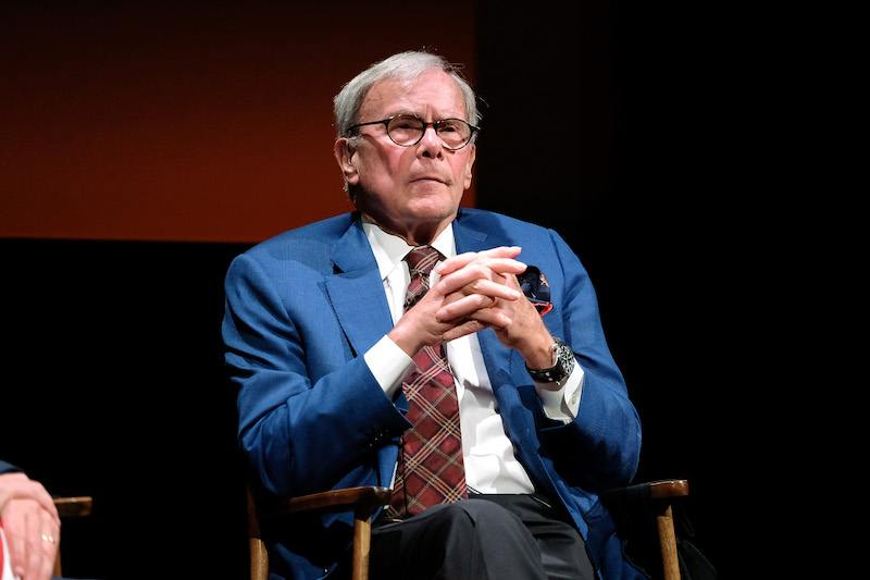 Tom Brokaw sits on a chair with his fingers clasped together.