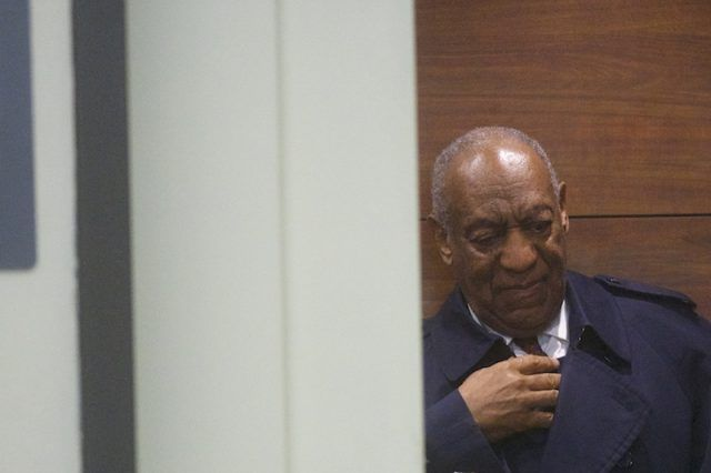 Bill Cosby leaning against a brown wall.