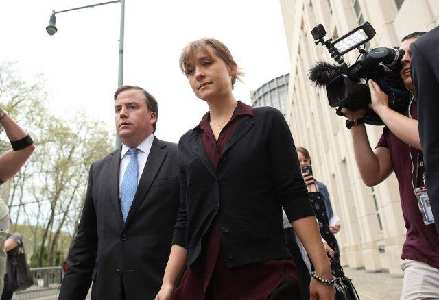Allison Mack walking past reporters.