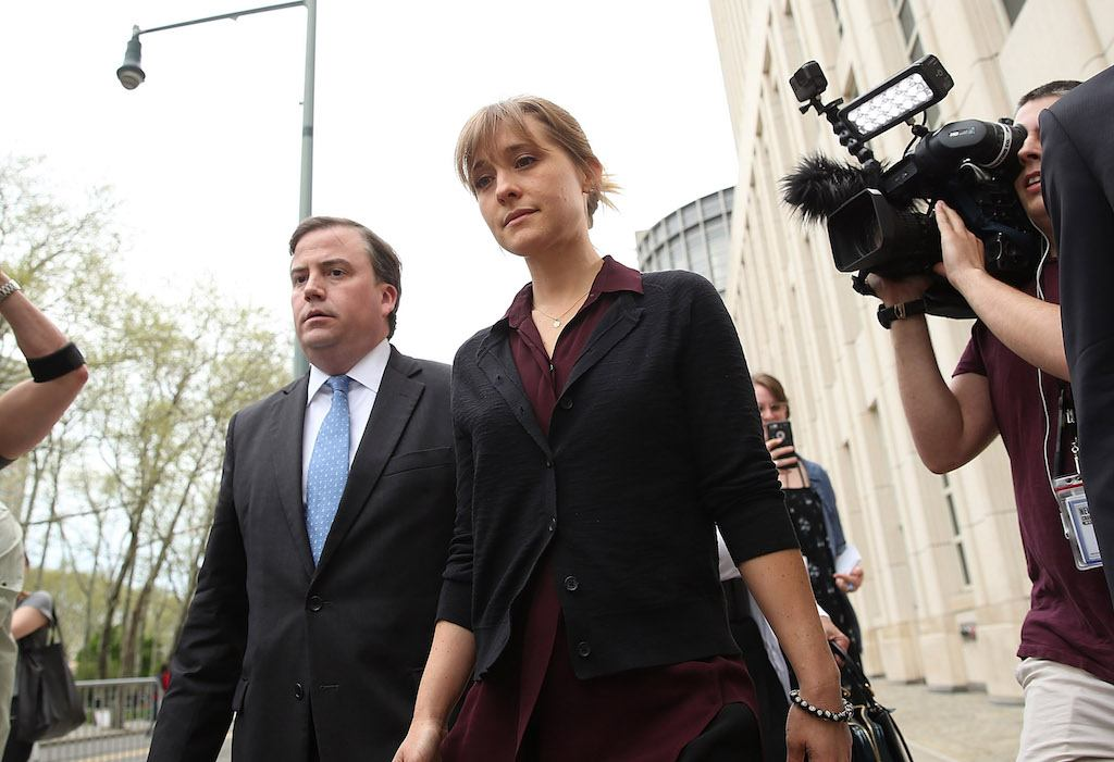 NEW YORK, NY - MAY 04: Actress Allison Mack (C) departs the United States Eastern District Court after a bail hearing in relation to the sex trafficking charges filed against her on May 4, 2018 in the Brooklyn borough of New York City. The actress, known for her role on 'Smallville', is charged with sex trafficking. Along with alleged cult leader Keith Raniere, prosecutors say Mack recruited women to a upstate New york mentorship group NXIVM that turned them into sex slaves. (Photo by Jemal Countess/Getty Images)