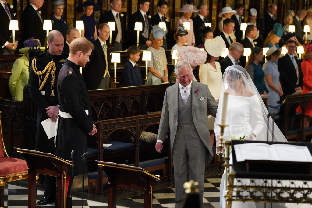 Prince Harry looks at his bride, Meghan Markle, as she arrives accompanied by Prince Charles, Prince of Wales during their wedding in St George's Chapel at Windsor Castle on May 19, 2018 in Windsor, England.
