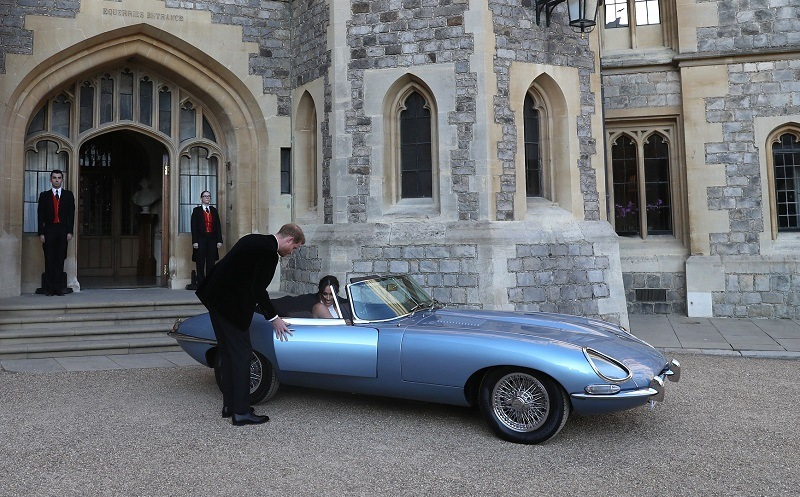 Britain's Prince Harry, Duke of Sussex, (L) opens the passenger door of an E-Type Jaguar car for his wife Meghan Markle, Duchess of Sussex, (R) as they leave Windsor Castle in Windsor on May 19, 2018 after their wedding to attend an evening reception at Frogmore House.
