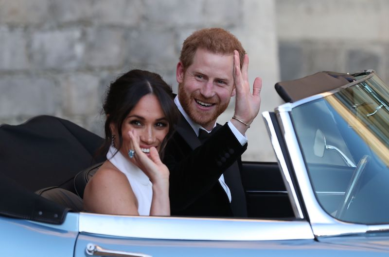 Britain's Prince Harry, Duke of Sussex, (R) and Meghan Markle, Duchess of Sussex, (L) leave Windsor Castle in Windsor on May 19, 2018 in an E-Type Jaguar after their wedding to attend an evening reception at Frogmore House. (Photo by Steve Parsons / POOL / AFP) (Photo credit should read STEVE PARSONS/AFP/Getty Images)