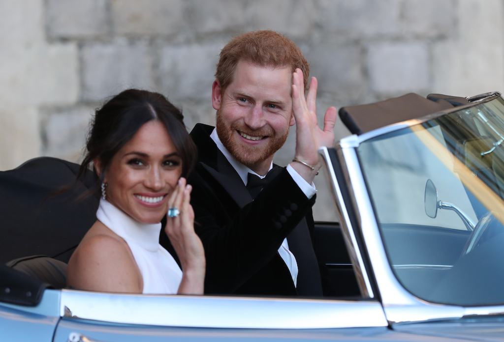 Duchess of Sussex and Prince Harry, Duke of Sussex wave as they leave Windsor Castle after their wedding to attend an evening reception at Frogmore House, hosted by the Prince of Wales on May 19, 2018 in Windsor, England.