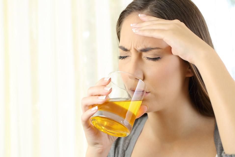 Girl suffering headache drinking a medicine
