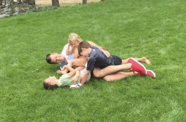Gisele and Tom in a huddle with their children.