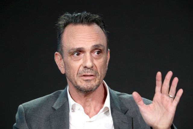Hank Azaria raising up his hand during a stage talk.