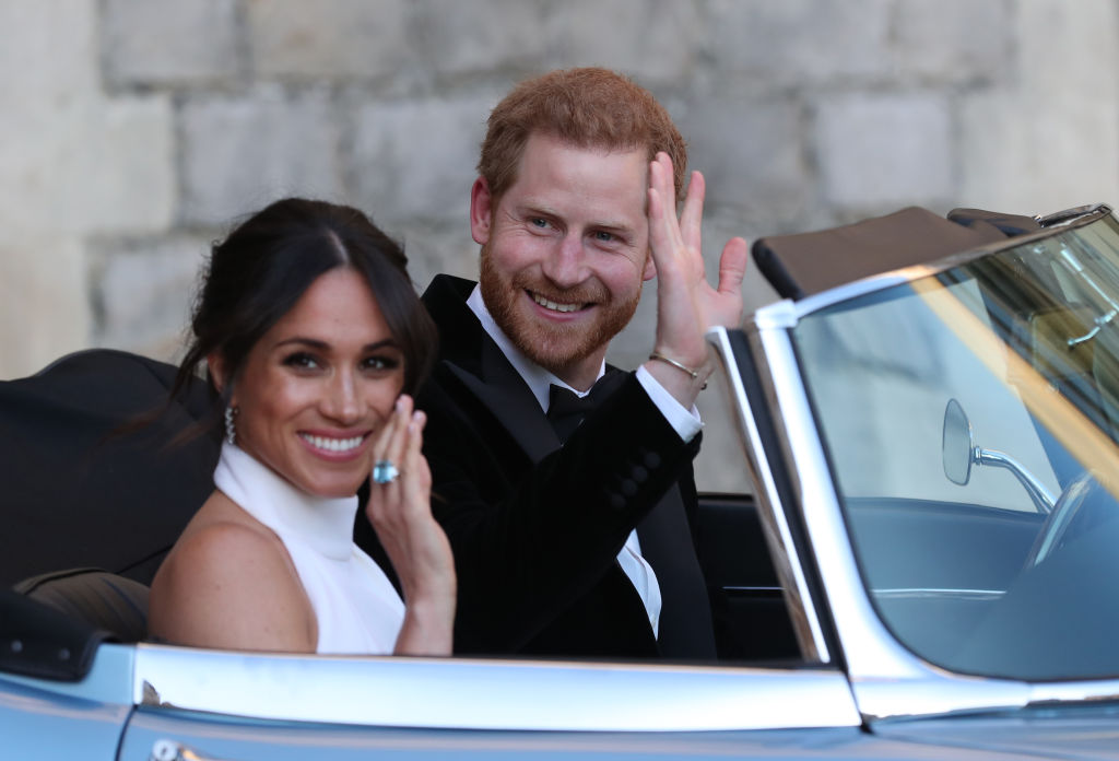 Duchess of Sussex and Prince Harry, Duke of Sussex wave as they leave Windsor Castle