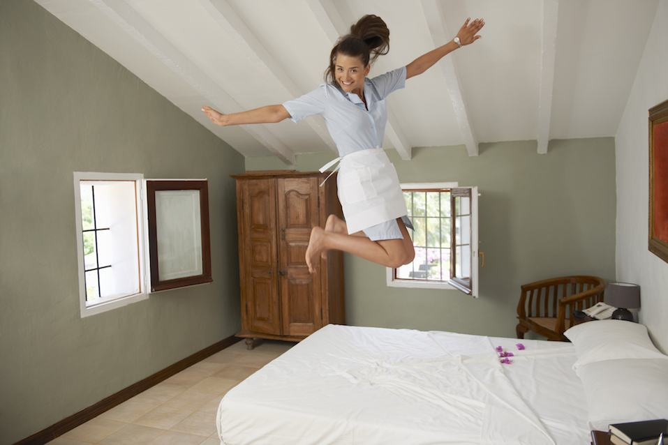 Women jumping on bed in room