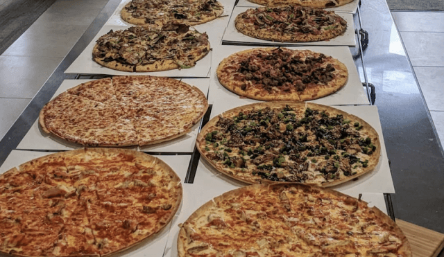 Pizzas set up on a table.
