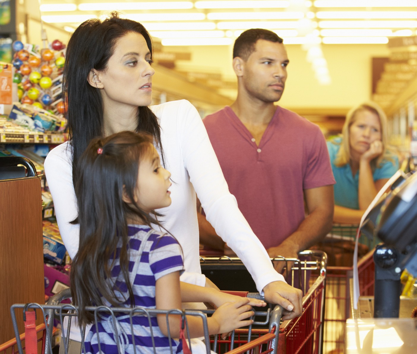 Customer In Queue To Pay For Shopping At Supermarket Checkout